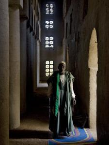 Imam of Kotaka Pauses Beside an Archway Inside the Impressive Mosque on Banks of Niger River, Mali by Nigel Pavitt
