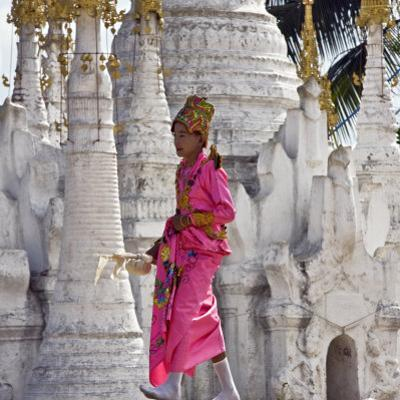 Myanmar, Burma, Lake Inle, A Young Novitiate Passes an Ornate Buddhist Shrine by Nigel Pavitt