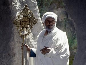 Old Ethiopian Orthodox Priest Holds a Large Brass Coptic Cross at Rock-Hewn Church of Adadi Maryam by Nigel Pavitt