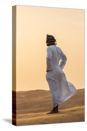 Oman, Wahiba Sands. an Omani Guide Enjoys the Sunset on Sand Dunes in Wahiba Sands.