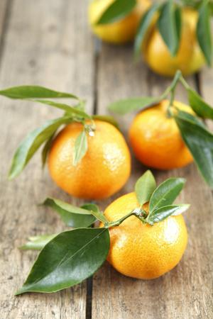 Clementines with Leaves on Wood