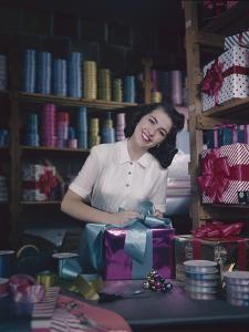 A Macy's Employee Ties a Bow onto a Present at a Gift Wrapping Counter, New York, New York, 1948 by Nina Leen