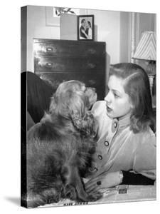Actress Lauren Bacall Chatting with Her Cocker Spaniel Dog in Her Suite at Gotham Hotel by Nina Leen