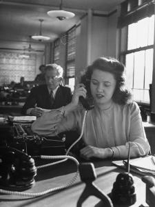 American Working Woman Sitting at Her Typewriter and Talking on the Telephone by Nina Leen