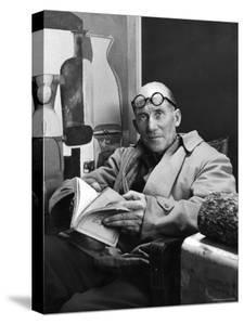 Architect Le Corbusier Sitting in Chair and Holding Book in Hands by Nina Leen