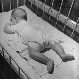 Baby Sleeping on its Stomach in Nursery at St. Vincent's Hospital by Nina Leen