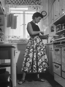 Career Girl Hostedd Joan Wilson in skirt and sleeveless blouse cooking in kitchen by Nina Leen