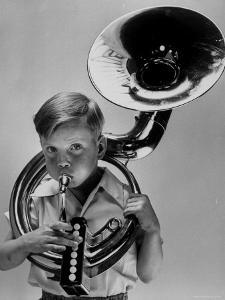 Child Playing Musical Instrument by Nina Leen