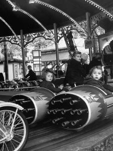 """Children Waiting Expectantly For a """"Rocket Ride"""" on the Carousel by Nina Leen"""