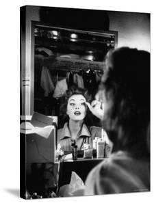 Debutante Actress Tina L. Meyer Putting on False Eyelashes in Dressing Room by Nina Leen