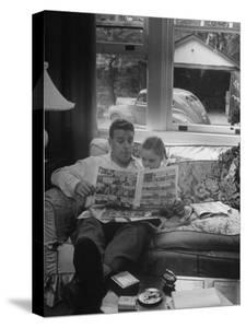 Father Sitting on Couch with Pigtailled Daughter Reading to Her the Sunday Comic Pages by Nina Leen