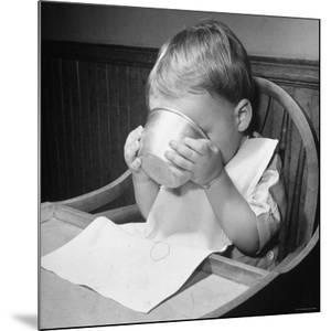 Fifteen Mo. Old Baby Demonstrates How He Can Now Drink from a Cup Even Though It is a Bit Sloppy by Nina Leen
