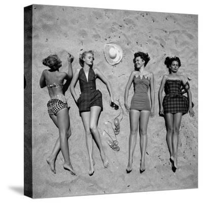 Four Models Showing Off the Latest Bathing Suit Fashions While Laying on a Sandy Florida Beach