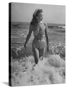 French Actress Barbara Laage Wearing Makeshift Two-Piece Bathing Suit Wading in Surf by Nina Leen