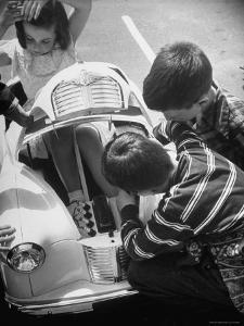 Girl Demurely Adjusting Her Hair While Willing Volunteers Repair Jammed Front Wheels of Her Car by Nina Leen