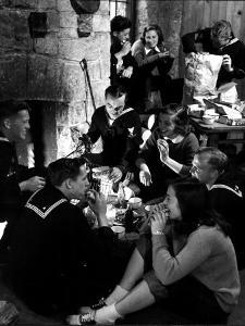 Group of Sailors and Young Ladies Sitting around a Fire Roasting Hot Dogs and Drinking Coke by Nina Leen