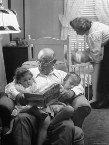 Harry Frantz Reading His Grandchildren to Sleep by Nina Leen