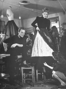 Jacques Fath Watching as the Tailor Hymns the Loose Ends at the Bottom of the Dress by Nina Leen