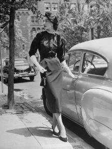 Katherine Cassidy Wearing a Red Fraostmann Wool Skirt and Black Sweater Beneath Black Cardigan by Nina Leen