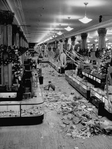 Macy's Department Store Employee Cleaning Up Piles of Debris after the Christmas Shopping Rush by Nina Leen