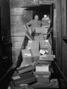 Macy's Department Store Employee Mike Reynolds Clearing the Package Chute with His Body by Nina Leen
