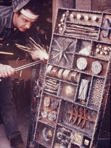 Maker of Metal Furniture, Paul Evans, Hope, PA., Burnishes Door of Steel Chest with Acetylene Torch by Nina Leen