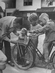 Man Fixing Basket on Bicycle as Children Watch Attentively by Nina Leen