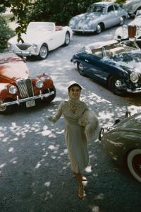 Model in a Dress and Gloves, a Fur over One Arm, and Surrounded by Vintage and Luxury Cars, 1954 by Nina Leen