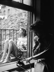 Model Jean Patchet Seated on a Fire Escape, Talks with Eileen Ford, New York, NY, 1948 by Nina Leen