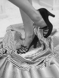Model Showing Off Satin Pumps for the Spring Season, at Saks Fifth Avenue by Nina Leen