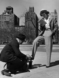 Model Showing Off Slacks as She Reads a First Aid Text Book in Washington Square Park by Nina Leen