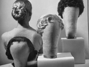 Model Vikki Dougan Wearing Attachable Bun of Extra Hair, Next to Other Wigs by Nina Leen