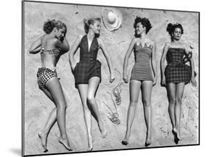Models Lying on Beach to Display Bathing Suits by Nina Leen