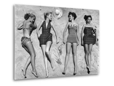 Models Lying on Beach to Display Bathing Suits