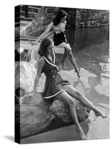 Pair of Models Showing Off New Bathing Suits on the Banks of the River by Nina Leen
