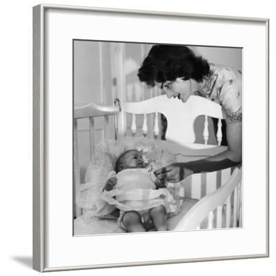 Sen. John Kennedy's Wife Jacqueline Offering Baby Caroline a Silver Rattle at their Georgetown Home