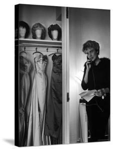 Singer Julie Wilson on Phone Beside Closet with Hanging Evening Dresses and Wigs on Top Shelf by Nina Leen