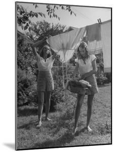 Teenage Twin Girls Hanging Laundry on Clothesline by Nina Leen