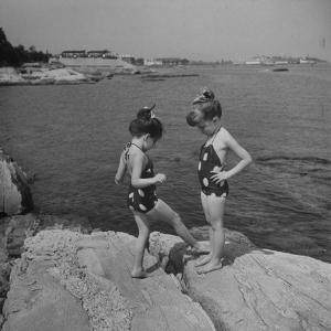 Two Little Girls Modelling Sun Dot Bathing Suits While Playing on the Rocks by Nina Leen