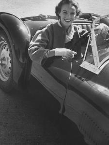 Well Dressed Woman Behind the Wheel of a Foreign Made Roadster by Nina Leen