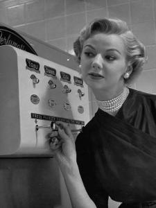 Woman Operating Coin-Operated Perfume Vending Machine by Nina Leen