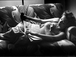 Woman Relaxing on Sofa, Reading and Drinking a Coke by Nina Leen