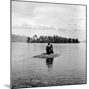 Young Couple Embracing on Small Rock Protruding from the Waters of Lake George by Nina Leen