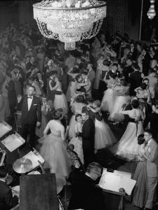 Young Couples at Formal Dance Dreamily Swaying on Crowded Floor of Dim, Chandelier-Lit Ballroom by Nina Leen