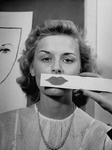 Young Girl Trying to Determine Which Lipstick Color Will Look Right with Her Complextion by Nina Leen