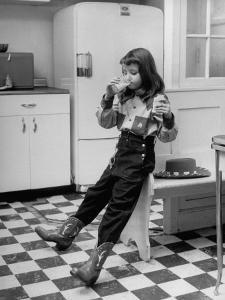 Young Girl Wearing Cowgirl Outfit Drinking Milk and Eating Sandwich in Kitchen by Nina Leen