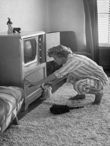 Young Woman Attending to Her Housework by Dusting Off Her Television Set by Nina Leen