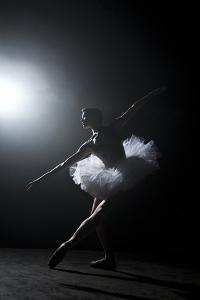 Ballerina Performing on Stage under Spotlight by Nisian Hughes