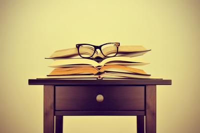 A Pile of Books and a Pair of Eyeglasses on a Desk, Symbolizing the Concept of Reading Habit or Stu