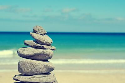 Stack of Balanced Stones in a White Sand Beach, with a Cross-Processed Effect
